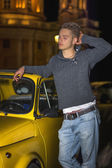 Night shot of young man standing next to small car — Stock Photo