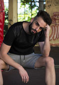 Handsome young man with beard, sitting and wearing t-shirt and shorts — Stock Photo