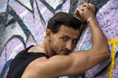 Handsome man leaning against graffiti wall — Stock Photo