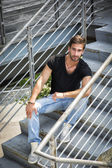 Handsome bearded young man sitting outdoors in urban environment — Stock Photo