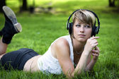 Beautiful young girl listening to music — Stock Photo