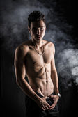 Lean athletic shirtless young man standing on dark background — Stock Photo