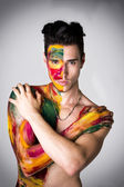 Attractive young man shirtless, skin painted all over with colors — Stock Photo