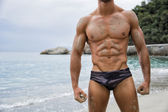 Strong muscular fit man posing in a swimsuit — Stock Photo