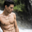 Handsome shirtless young man near mountain waterfall — Stock Photo