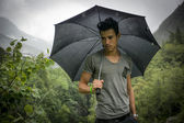 Young man in lush, green mountains holding an umbrella — Photo
