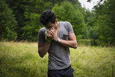 Young man outdoors sneezing in handkerchief — Stock Photo