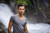 Handsome young man near mountain waterfall — Stock Photo