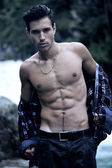 Handsome young man near mountain waterfall with open shirt — Stock Photo