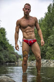Handsome young muscle man standing in water pond, naked — Stock Photo