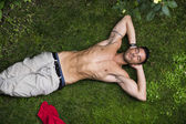 Fit male model lying on the grass — Stock Photo