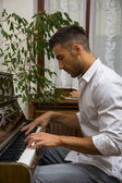 Male artist playing his classical upright piano — Stock Photo