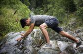 Man climb in lush green mountain scenery — Stock Photo