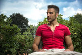 Fit male model sitting on bench — Stock Photo