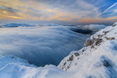 Sunset over the mountains and clouds in winter — Stock Photo