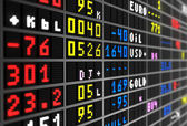 Colored stock ticker board on black — Stock Photo
