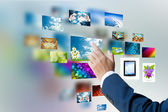 Men hand using touch screen interface with pictures in frames — Stock Photo