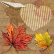 Autumn leaf with plane origami and heart — Stock Photo