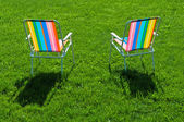 Two colorful chairs standing on grass — Stock Photo