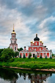 Red church on coast of the lake — Stock Photo