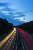 Long time exposure freeway cruising car light trails streaks of light highway electricity pylon sky — Stock Photo