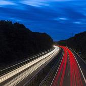 Long time exposure freeway cruising car light trails streaks of light highway electricity pylon sky — Stock Photo