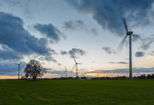 Wind turbine wind wind energy wind power wheels field sunset sky clouds dusk blurred — Stock Photo