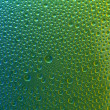 Water drops spectral green yellow blue gradient rainbow colorful beading lotuseffekt tau sealing — Stock Photo