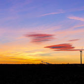 Sunrise windmill wind turbine winter energy Silhouette natural blue hour orange sunlight — Stock Photo