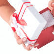 Hand with a gift with a red ribbon isolated on white background — Foto de Stock