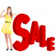 Smilling woman in yellow dress showing a sale word — Stock Photo