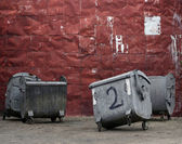 Red metal wall with garbage containers — Stock Photo