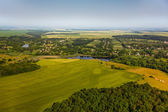 Aerial view above the village and green fields — Stock Photo
