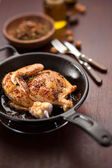 Roasted half chicken on black pan — Stock Photo