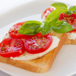 Bread with mozzarella tomatoes and basil — Stock Photo
