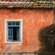 Stock Photo: Rusty wood blue window on aged orange wall
