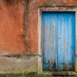 Front of abandoned house with blue door — Stock Photo #14862803