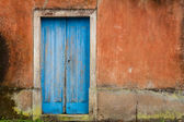 Front of abandoned house with blue door — Stock Photo
