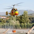 PENELA, PORTUGAL - AUGUST 28 : Fire rescue heavy helicopter, with water bucket, scooping water in Penela August 28, 2010 in Penela, PORTUGAL — Stock Photo