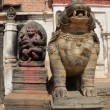 Nepal, Bhaktapur, Durbar square. The deity Hanuman and the stone lion near the entrance to the Royal Palace. — Stock Photo #17335413