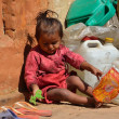 Stock Photo: Bhaktapur, Nepal, little girl plays at threshold of her house next to construction trash.