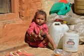 Bhaktapur, Nepal, little girl plays at the threshold of her house next to the construction trash. — Stock Photo