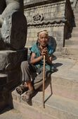 Poor elderly Nepalese man sitting on the steps of the Temple of Taumadhi square in Bhaktapure — Stock Photo