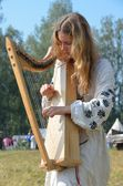 Young girl in Medieval clothing, playing on an old stringed musical instrument — Photo