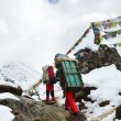 Nepal, trekking in the Himalayas, porters loaded on the trail — Stock Photo