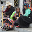 Stock Photo: Tibet, Lhasa, tibetiwomen sitting near ancient Jokhang temple.