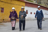 Elderly Tibetans commit the bark around the Potala Palace in Lhasa — Stock Photo
