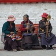 Tibet, Lhasa, three elderly women sitting on a bench near the Temple  Djokang — Stok fotoğraf