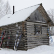 Stock Photo: Arkhangelsk region, ski trip, skies lean to a wall of wooden houses during a halt