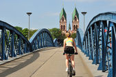 Cyclist passing a bridge — Stock Photo